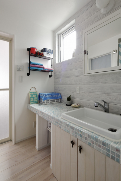 モザイクが爽やかな洗面台を造作した洗面室の様子