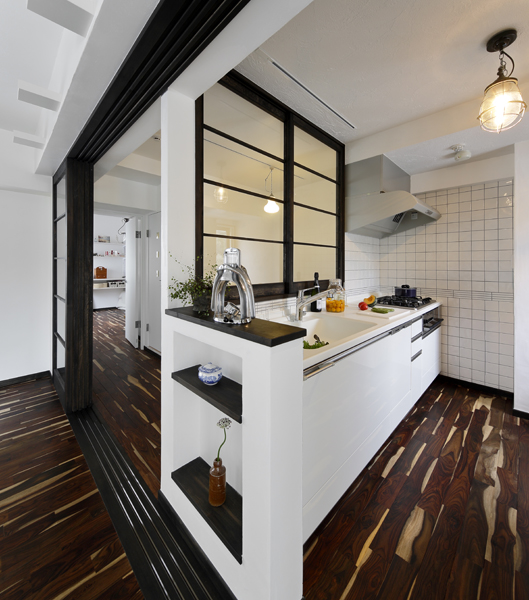 ガラス仕様の間仕切りで隣室と区切ったキッチンの様子