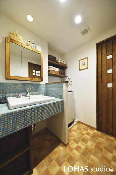 モザイクタイルであしらった洗面台のある洗面室の様子