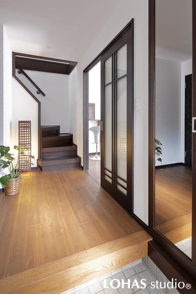 透明感のある建具と鏡の効果で光を感じる玄関の様子