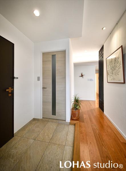 間仕切りのダーク色で引き締まった玄関の様子