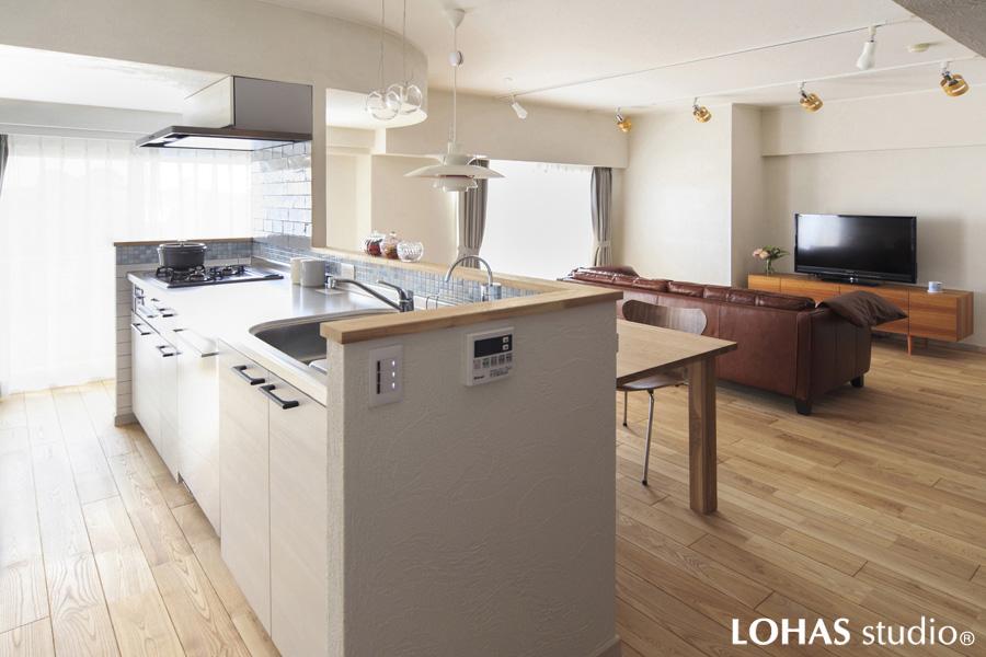 白いキッチンが印象的な明るいLDKの様子