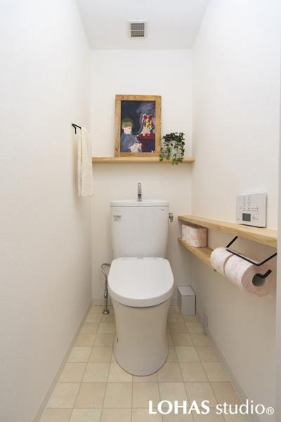 無垢アッシュ材でカウンターや棚を造作したトイレの様子