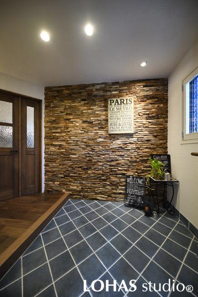 チークの古材を再利用した壁がゲストをもてなす玄関の様子
